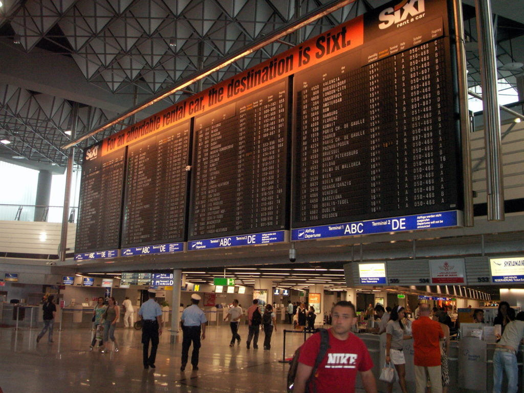An airport terminal with a massive information board. There are people walking through the terminal.